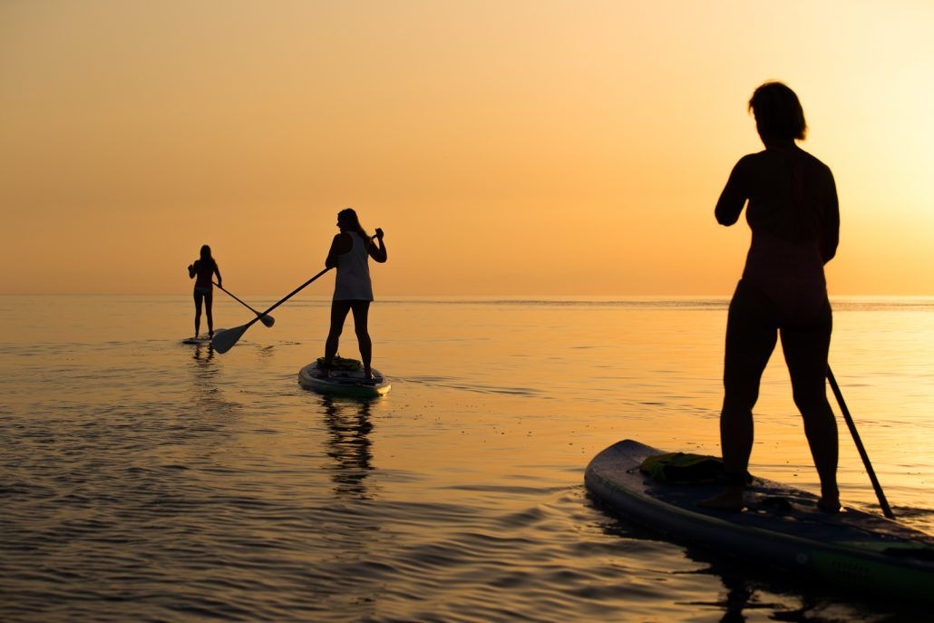 Three women paddling as the sun rises in Rhodes